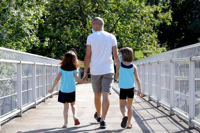 Un padre a passeggio con i figli