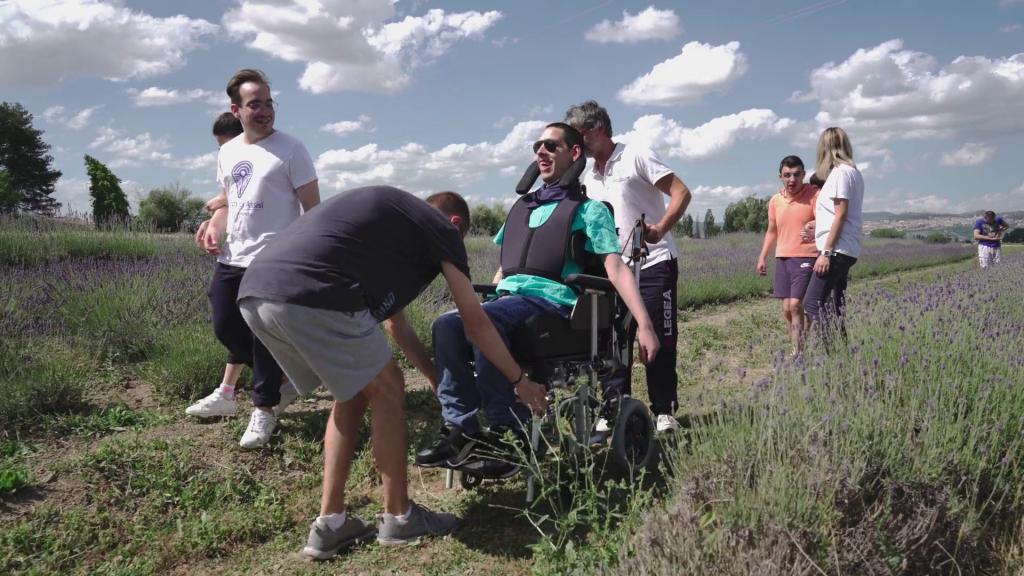 Operatori aiutano un ospite in carrozzina dell'Istituto Serafico